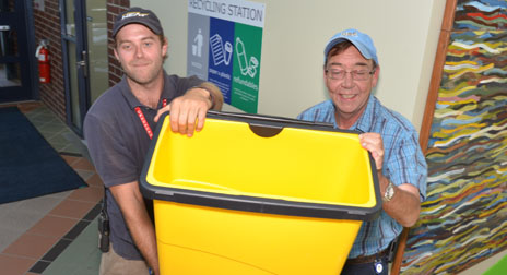 Rudy Sager and Al King from Facilities Management hoist one of the new yellow compost bins now located in the foyers of each building on campus.