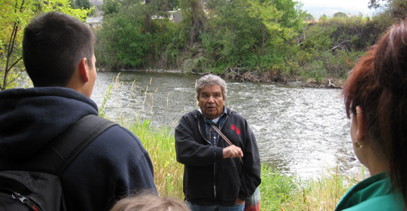 En'owkin Centre language instructor Richard Armstrong gives an informal orientation about the Okanagan Nation Alliance Salmon Feast on the banks of the Okanogan River.
