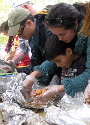 International student Claudia Donoso, from Ecuador, helps her son Nacho take part in the fish deboning work next to the underground cooking pit.