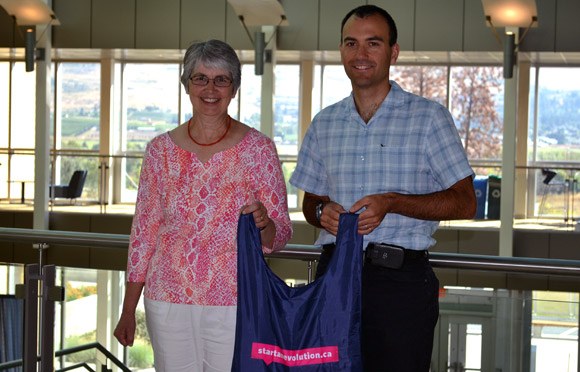 start an evolution Faculty and Staff lead volunteer Louise Nelson presents André Phillion, with his travel package prize.