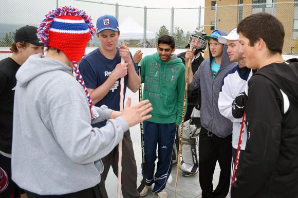 After the games is tied in regulation, RezLetics Road Hockey Tournament organizer Mike van Nostrand, red toque, flips a coin to decide which team will shoot first in a shoot-out while former rep hockey player Tom Menard, far right, looks on.