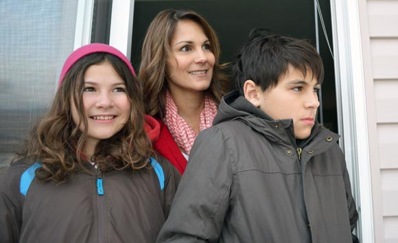 Amber Froste looks out from her Vernon balcony with her children