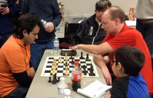Jose Yunier Bello Cruz (left) plays Graham Swett in the final match of the tournament as fellow competitors look on.