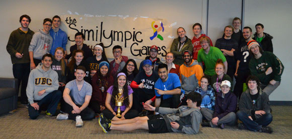 Inaugural Similympics competitors pose for a group shot while Team Purple shows off their gold-looking trophy.