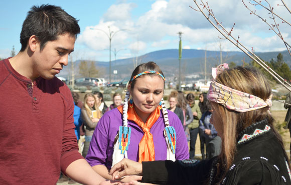 At the Tree Planting Ceremony on March 21, Westbank First Nation Elder Delphine Derickson passes out tobacco to Hailey Causton and fellow Okanagan Nation member Nicholas Clark to place in the ground underneath the tree.