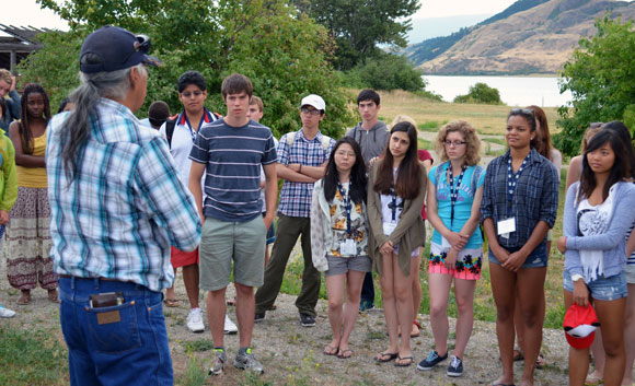 Okanagan Nation Elder Eric Mitchell provides a cultural context to the land to visiting students just outside the door of the Okanagan Indian Band Winter House.