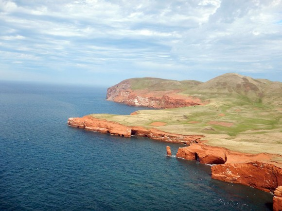 The Entry Island coast with lines of sedimentary deposits distinct from the basalt base of the hills in the background. The sea is moving the coastline inward. (Photo credit: Robin Dods)