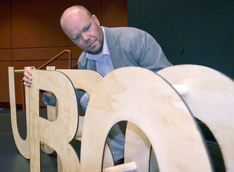 Commuter Student Coordinator Greg Mather lines up the 'UBCO' wooden blocks on stage in the University Theatre. Mather also acted as emcee for the second annual IAN Talks.
