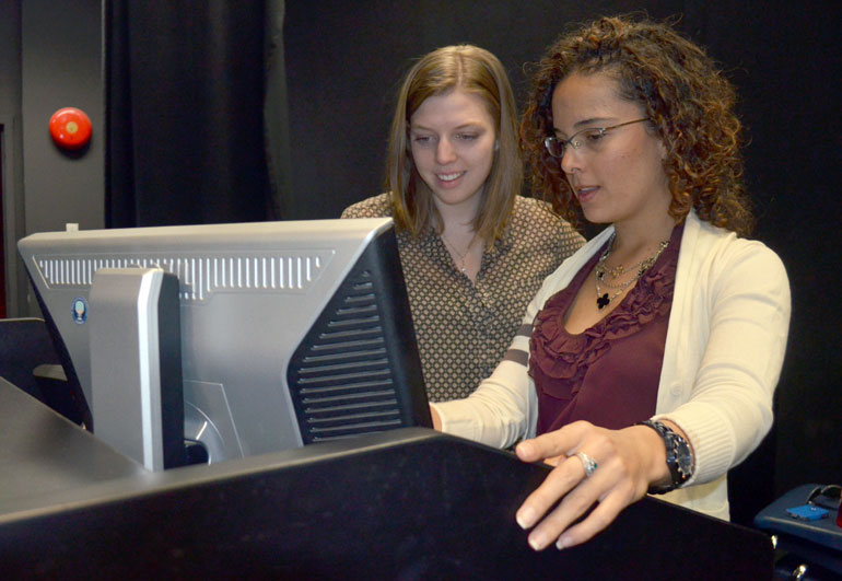 Backstage, Campus Life student volunteer Sydney Bednarik, left, goes over the audio visual format with First Year Services Coordinator Laura Prada. Campus Life is credited for coordinating IAN Talks for the past two years.