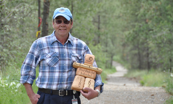 Allan King, former manager of maintenance and grounds, with the City of Kelowna's Most Environmentally Dedicated Individual award he won in 2010. Behind him is the campus trail system, one of the many campus sustainability initiatives King has championed over the years.