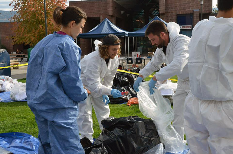 Facilities Management's Kirt Stewart (right) and two student volunteers sort through trash and recyclables at the 2014 Campus Waste Audit.