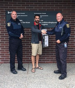 Campus Security's Mike Gesi (left) and Paul Hipsey (right) return a stolen portable weather station to Environment Canada meteorologist Doug Lundquist.