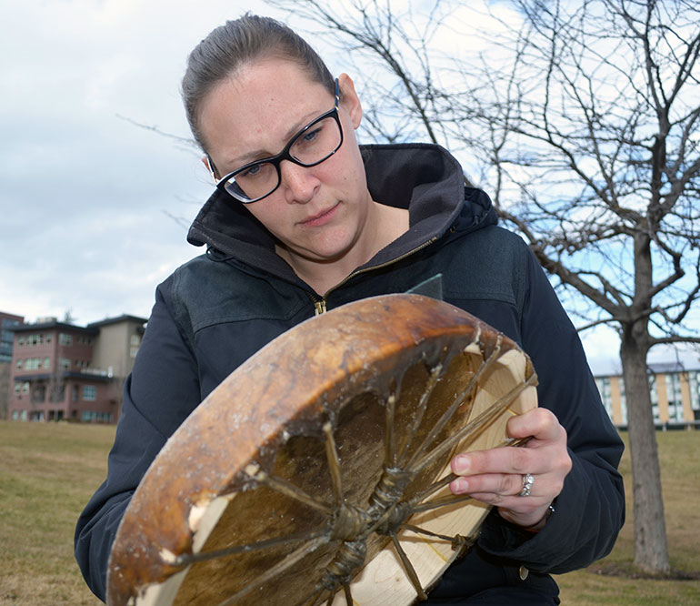 The Aboriginal Programs & Services Drum Making event took place outside UNC over a weekend. After her drum dried, Academic Advisor Jessica Beck used her lunch break to sand the rough patches off the moose hide.