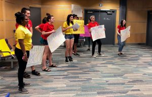 Peer Leaders and Senior Peer Leaders form a greeting squad at the airport