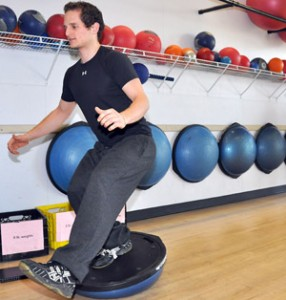 Human Kinetics student Stefan Bigsby practices a training exercise on the BOSU ball at iQuest Healthcare and Fitness Centre.
