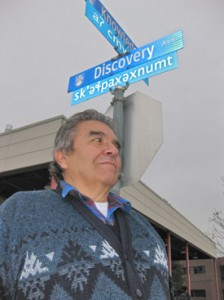 Okanagan Language instructor Richard Armstrong stands with one of the new street signs on UBC's Okanagan campus. The Penticton Indian Band member is a driving force in keeping the culture of the Okanagan Nation alive for future generations.