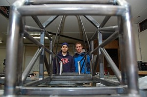 Engineering students Scott Ghomeshi and Chris Lambert through the metal frame of the UBCO Motorsports race car they and classmates are building.