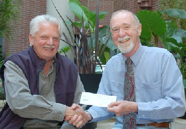 Myra Canyon Trestle Restoration Society President Carl Marcotte, left, presents a cheque for $10,000 to UBC Okanagan History Professor Maury Williams, to support research into the Myra Canyon trestles' history and future