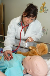 UBC Okanagan Nursing student Lia Bartolillo checks the chest sounds of the School of Nursing's new pediatric human patient simulator, nicknamed Dylan.