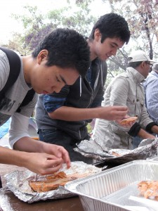UBC international student Morio Fukunaga, left, from Japan and Aboriginal student Cody Tolmie take part in the sockeye salmon deboning session of the Okanagan Nation Alliance Salmon Feast in Okanagan Falls. (Photo: Dan Odenbach)