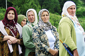 Grieving women pass by the stone marker at the Potocari memorial site for victims of the 1995 Srebrenica massacre, in which 8,000 Bosnian Muslim men and boys were massacred by Serb forces - photo by Adam Jones