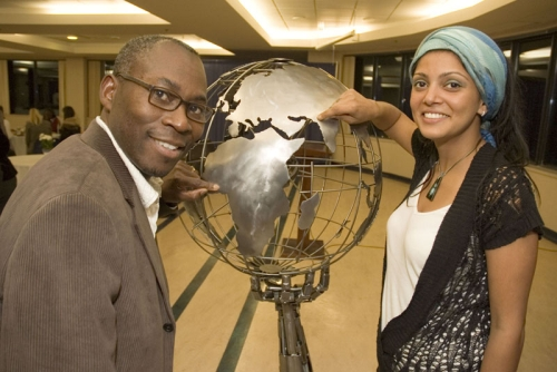 Chris Ellom, with the organization Smile Africa, and Bhavana Kapal, a third-year social work student at UBC Okanagan, point to their hometowns – Accra, Ghana, and New Delhi, India -- on a metal sculpture presented to UBC Monday night by Vernon artist Cory Fuhr.