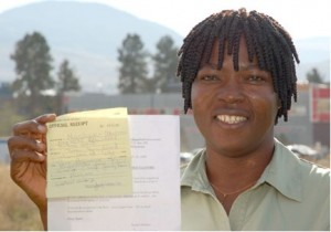 Vida Yakong, Master of Science in Nursing student, holds the receipt for registering a northern Ghana women's group with the Red Cross. Registered groups can have foreign donations delivered across Ghana by the Red Cross at no cost.