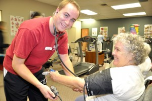 Fourth-year UBC Human Kinetics student Shaun Crowell takes the blood pressure of a client at COACH as part of his volunteer work term.