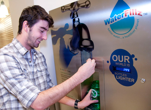 Spencer Robins, Services Coordinator for the Students' Union, fills his reusable water bottle at the new water kiosk in UBC's Arts and Sciences II building.