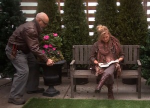A passer-by (Don Burnett) uses greenery to turn a drab bench into a warm and inviting reading space (avid reader played by Elaine Crebo MacLeod).