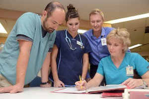 Gord Binsted, left, Acting Dean, Faculty of Health and Social Development at UBC's Okanagan campus, Lauren Sugie of Calgary, second-year nursing student, Loyd Busby, nurse manager, Kelowna General Hospital 4A and Associate Professor Wendy Andrews, of UBC's School of Nursing, review a patient chart during a clinical learning session. Binsted spent a day in the hospital with the nursing students and was impressed with what he saw.