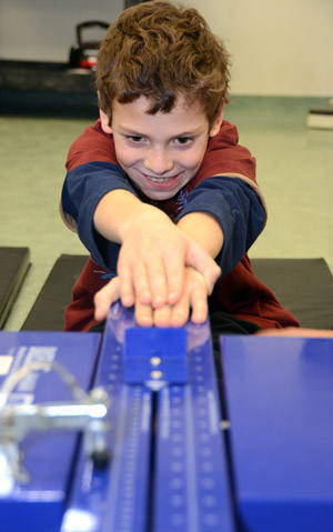 Grade 5 Casorso Elementary student Anthony Kurkjian tests his flexibility in the Human Kinetics lab at the University of British Columbia's Okanagan campus. The elementary students had the opportunity to add to their book lessons by getting some hands-on experience thanks to their teacher and the Schools of Nursing and Health and Exercise Sciences.