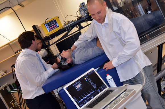 UBC PhD student Chris Willie, right, conducts a procedure on another student using a NASA-designed lower body negative and positive pressure box in a Centre for Heart, Lung and Vascular Health lab.