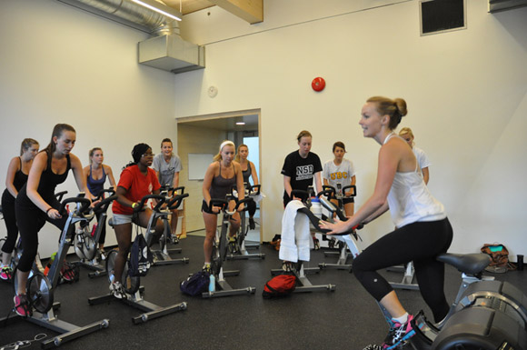Graduate student Ayla Graham leads a spin class in the Hangar's downstairs studio, proving to be a popular fitness outlet with students.