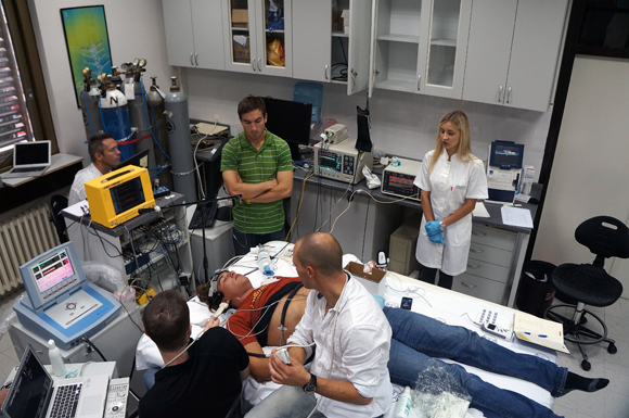 Anthony Bains, left, and Chris Willie, second from left, monitor readings. Prof. Philip Ainslie, (white shirt, rear) monitors another piece of equipment