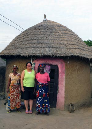 Muriel Kranabetter, centre, seen with local women outside a typical mud hut in Chanshegu, Ghana.