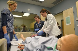 UBC nursing student Christine Gregory and medical students Alison Leighton and Robyn Buna work to solve a patient emergency in the Pritchard Simulation Centre.