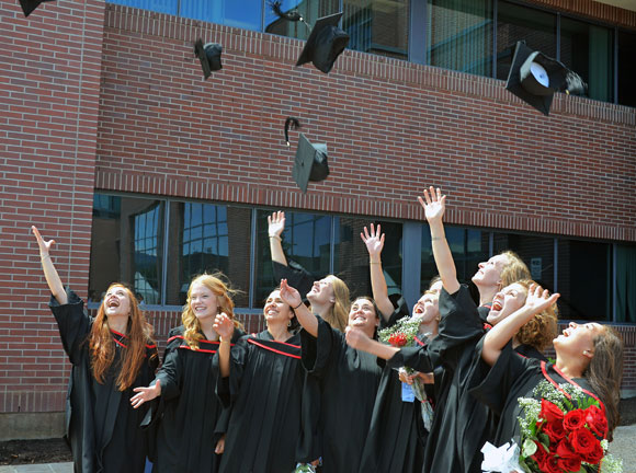 School of Nursing graduates toss their mortarboards in the air at the 2013 Convocation