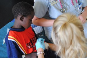 School of Nursing students do a painful dressing change on a young Zambian boy at Lewanika General Hospital in Zambia during a 2012 practicum. There were no pain medications to give to their patient.