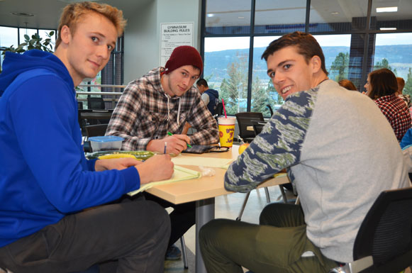 UBC Heat volleyball teammates Jim Bell, Josh Harvey, and Kristof Schlagintweit, far left, pull out the books during a lunch break at the gym.