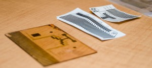 "Digital microfluidic chips can be made on glass wafers, left, but UBC researchers have developed a screen-printing approach that allows them to quickly ""print"" several yards of these chips on paper."