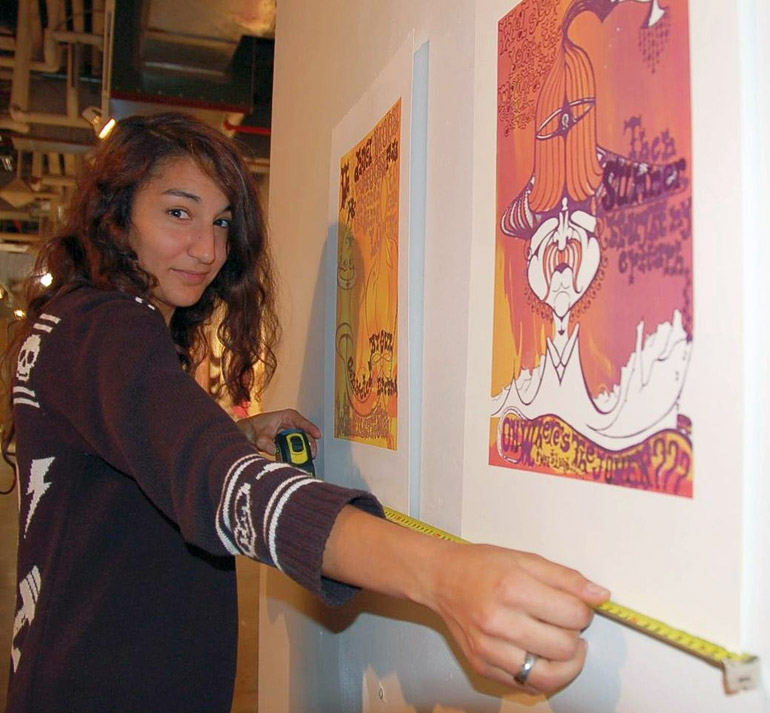 Petra-Celli Kanbour measures wall space for her print-making exhibit at Shelf Life, an exhibition of bachelor of fine arts graduates majoring in visual arts.