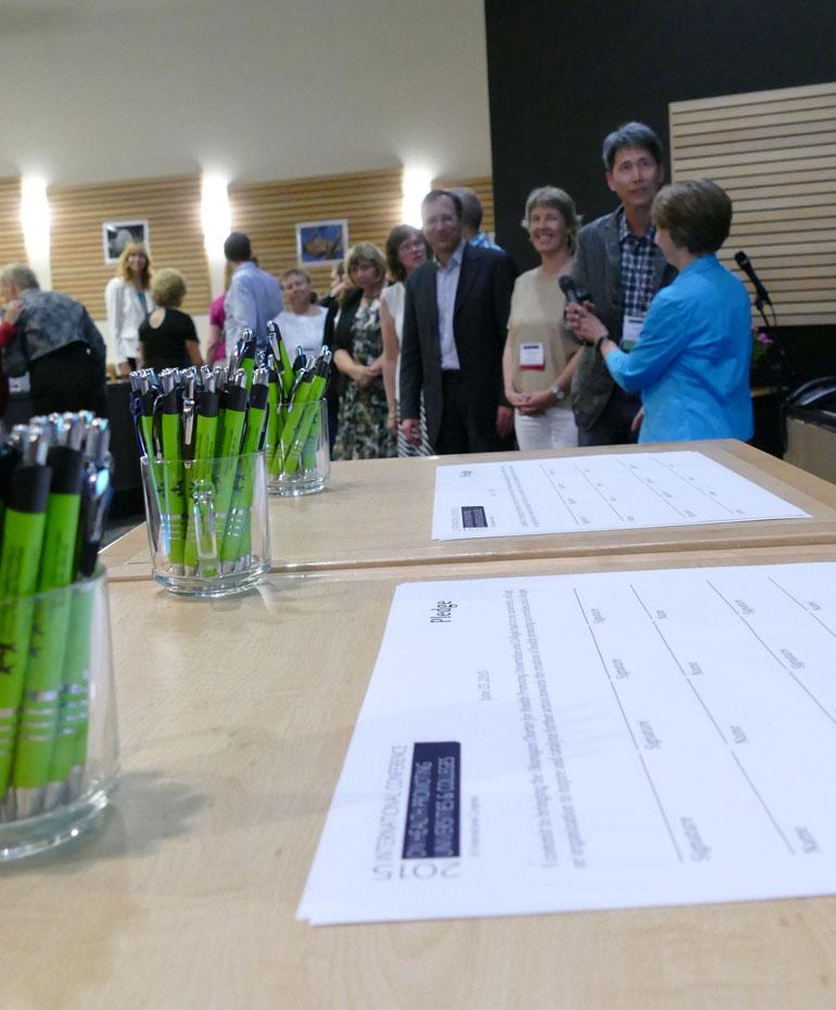 Conference delegates prepare to sign the Okanagan Charter Thursday afternoon at UBC Okanagan.