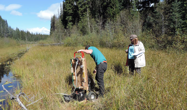 UBC professor Deborah Roberts supervises student Keith Story as he sets up test equipment on a creek in a cattle grazing area.