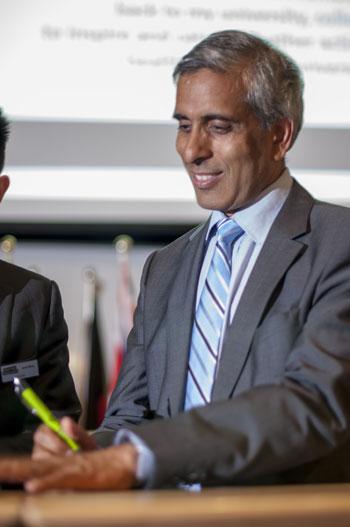 UBC President Arvind Gupta adds the first signature to the Okanagan Charter Thursday afternoon at UBC Okanagan.