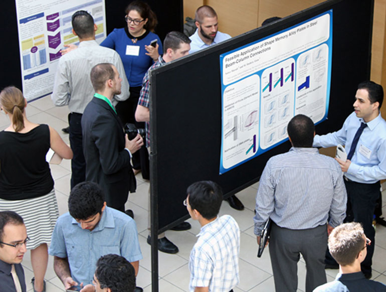 Civil engineering student Saber Moradi, far right, explains his poster display highlighting his research theories to improve seismic performance in buildings.