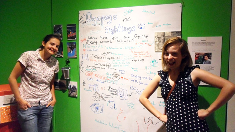 "Cultural Studies student Lauren Richardson and History student Samantha Steenwyk encourage people to share their ""sightings"" of Ogopogo toys, sculptures, and other images they see in the Kelowna community. Their Ogopogo display is at the Okanagan Heritage Museum until the end of August."