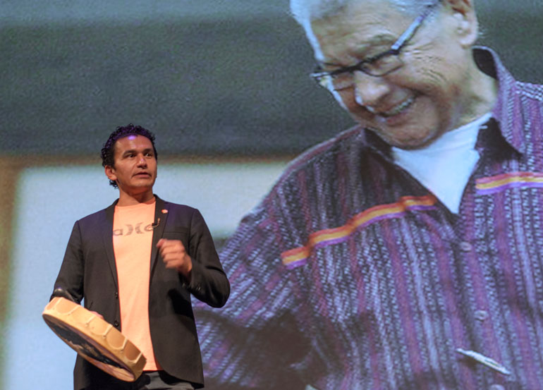 With a superimposed image of his father behind him, Wab Kinew discusses a song he wrote shortly after his dad's death. Kinew played four songs in his traditional language, and the audience responded with a standing ovation.