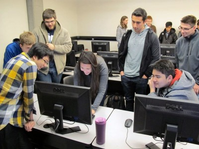 Eric Huang, far left, and Shannon Farvolden (leaning over computer) demonstrate some basic computer skills to students from KSS during UBC Okanagan's recent Computer Science Day.