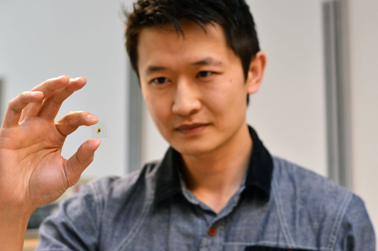 UBC's Kenneth Chau holds a glass sample used in his latest research, which proved that putting thin layers of metal over glass increases light transmission.